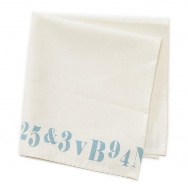 Serviette beige mit Zahlen + Buchstaben an einer Kante , 45 x 45 cm mit einem Fleck
